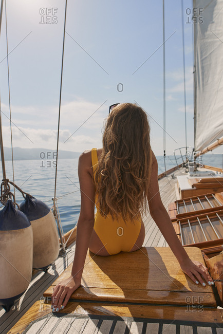 Beautiful woman on sailboat in bikini in ocean on luxury summer lifestyle happy adventure travel vacation