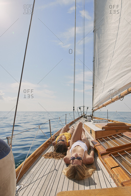Beautiful women sunbathing on sailboat in ocean on luxury lifestyle happy adventure travel vacation