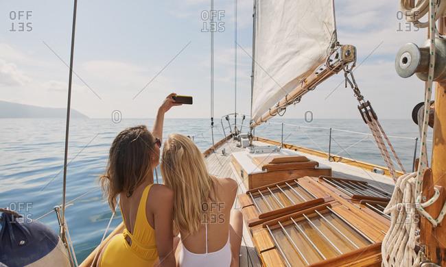 Beautiful women friends taking selfies smart phone social media on sailboat in ocean on luxury lifestyle adventure travel vacation