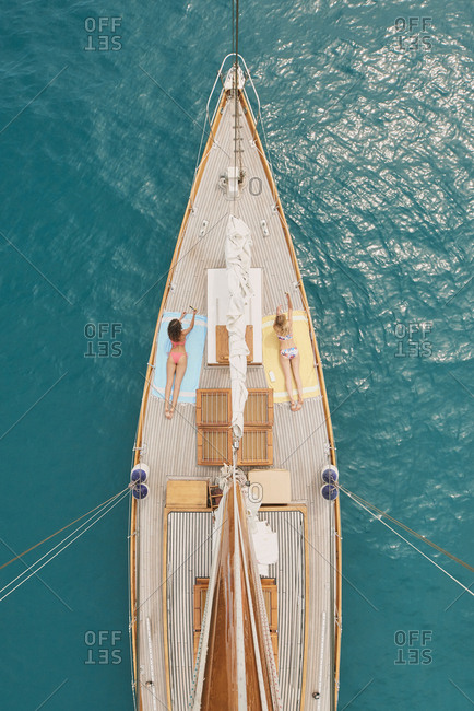 Beautiful girl friends on sailboat in ocean from above overhead on luxury lifestyle adventure travel vacation