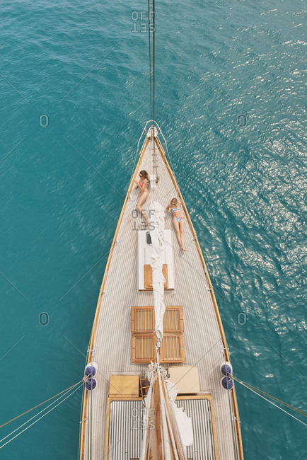 Beautiful girl friends tanning on sailboat in ocean from above overhead on luxury lifestyle adventure travel vacation