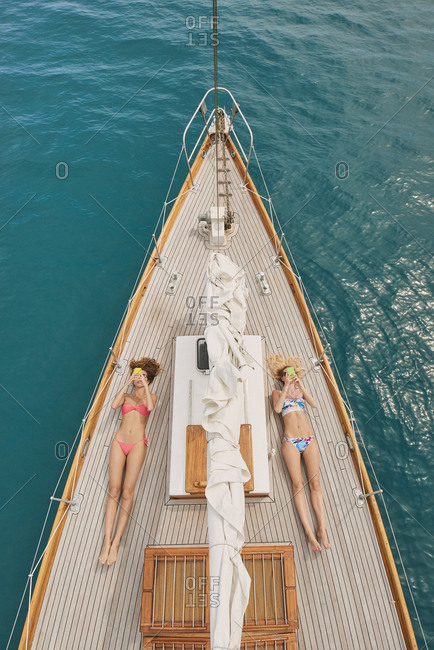 Beautiful girl friends on sailboat using smart phone technology for social media in ocean from above overhead on luxury lifestyle adventure travel vacation