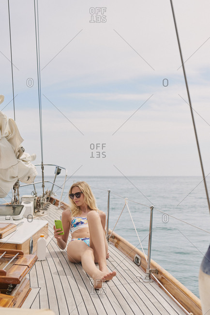 Beautiful girl on sailboat using smart phone technology for social media in ocean on luxury lifestyle adventure travel vacation