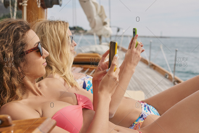 Beautiful girl friends on sailboat using smart phone technology for social media in ocean on luxury lifestyle adventure travel vacation