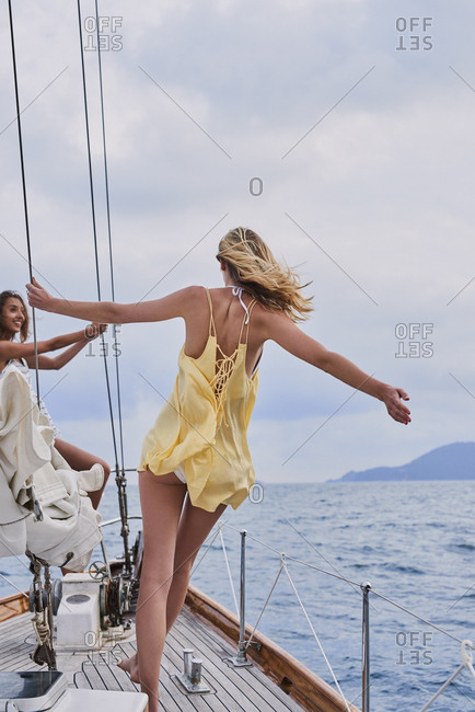 Beautiful girl friends on sailboat in ocean on luxury lifestyle happy adventure travel vacation