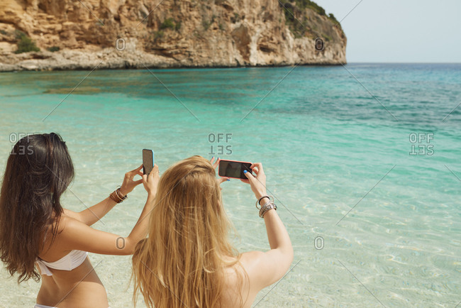 Beautiful girl friends taking photos with smart phone technology on paradise beach destination summer wanderlust vacation