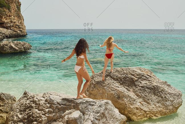 Beautiful girl friends rock jump on beautiful beach carefree wild travel adventure vacation