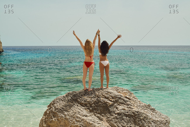 Adventure beautiful friends arms raised on paradise beach on destination summer wanderlust vacation
