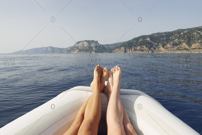 Beautiful girl friends feet travel on speed boat to paradise island for relaxing nature tourist destination vacation discover explore