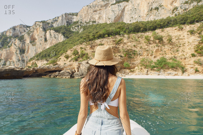 Beautiful woman on speed boat driving to paradise beach island discover summer adventure vacation