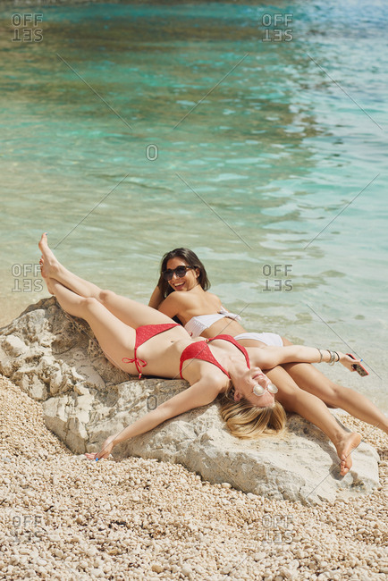 beautiful girl friends relaxing on paradise beach on destination summer wanderlust vacation