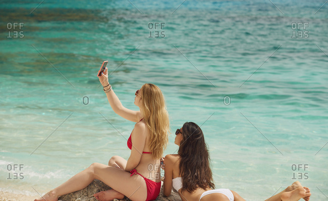Beautiful girl friends taking selfies with smart phone technology on paradise beach destination summer wanderlust vacation
