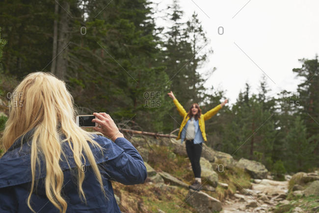 Girl taking photo of friend with smart phone for social media on travel adventure beautiful forest landscape