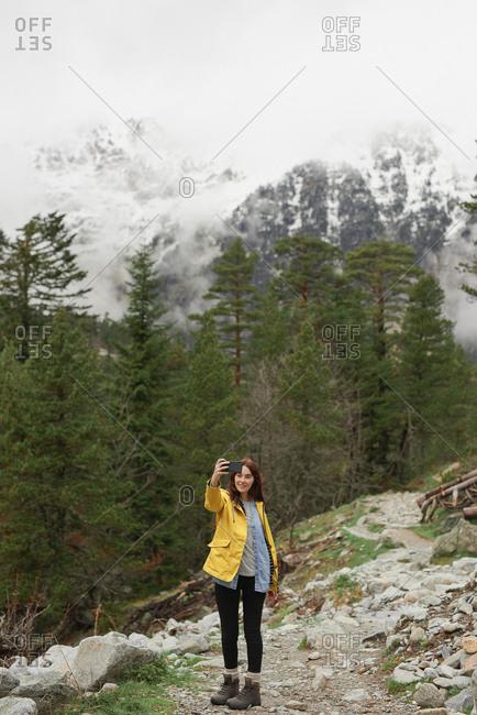 Travel adventure woman taking smart phone selfies on mountain enjoying beautiful nature landscape wanderlust
