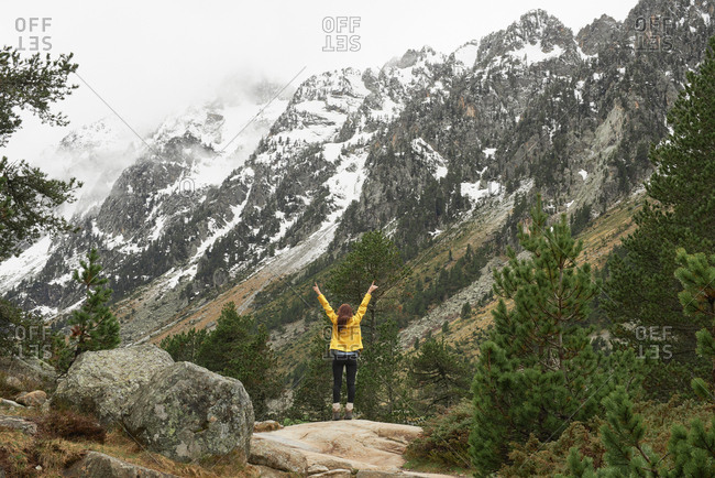 Travel adventure hiker woman celebrates arms outstretched enjoying beautiful nature forest landscape wanderlust