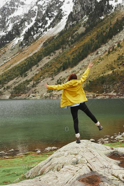 Travel adventure hiker woman celebrates on mountain lake arms outstretched enjoying beautiful nature landscape wanderlust