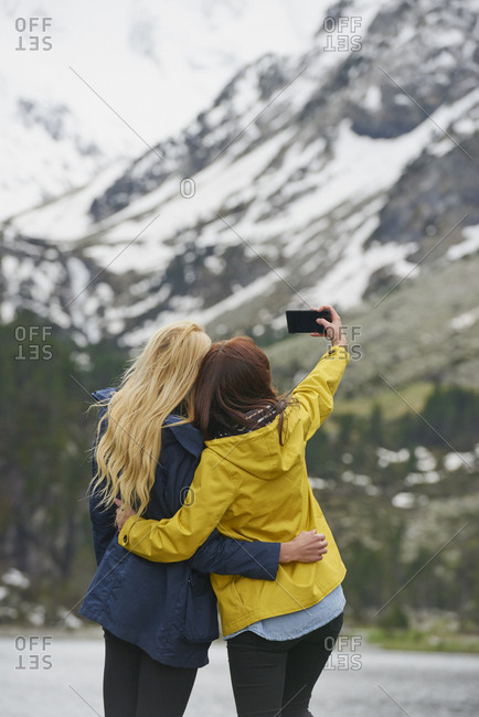 Travel adventure woman friends taking smart phone selfies on mountain lake enjoying beautiful nature landscape wanderlust