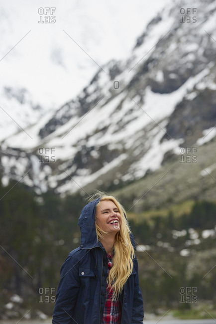 Portrait of Adventure travel hiker woman smiling  in beautiful green forest snow mountains on scenic outdoor vacation
