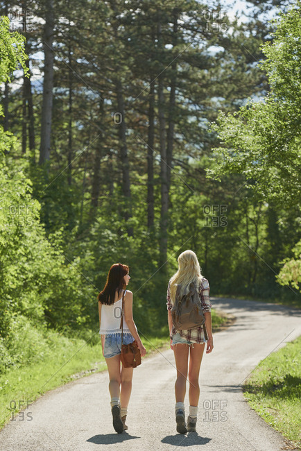 Traveler girl friends walking countryside road on wanderlust adventure vacation