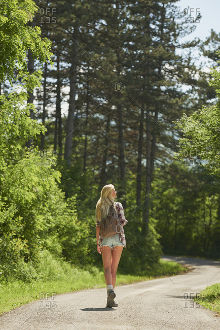 Traveler girl walking alone forest countryside road on wanderlust adventure vacation