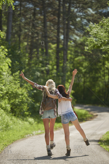 Traveller backpack happy girl friends dancing on scenic countryside road on wild adventure vacation