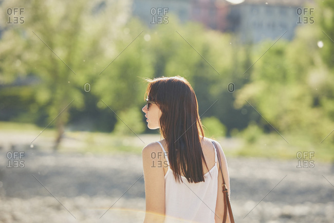 Dreamy Portrait of beautiful woman in sunlight flare exploring travel destination on vacation