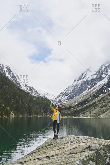 Travel adventure woman taking smart phone selfies on mountain lake enjoying beautiful nature landscape wanderlust