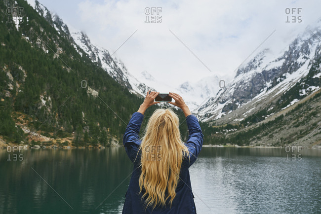 Travel adventure woman taking smart phone photograph on mountain lake enjoying beautiful nature landscape wanderlust