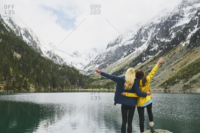 Travel adventure hiker woman friends celebrate on mountain lake arms outstretched enjoying beautiful nature landscape wanderlust