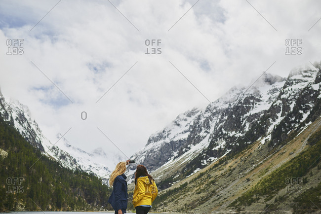 Travel adventure woman friends taking smart phone photograph on mountain lake enjoying beautiful nature landscape wanderlust