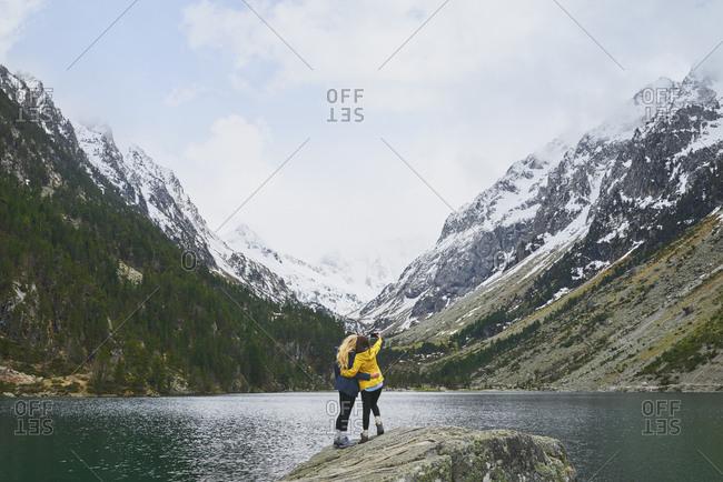 Travel adventure woman friends taking smart phone selfies on mountain lake enjoying beautiful nature landscape wanderlust