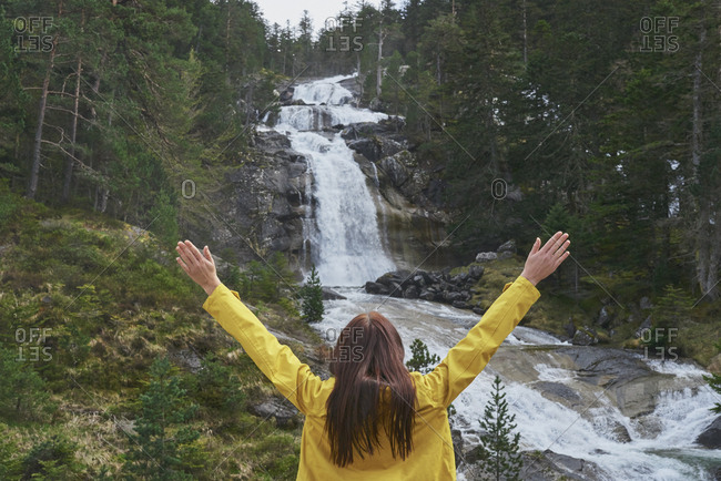 Travel adventure hiker woman celebrates arms outstretched at waterfall enjoying beautiful nature landscape wanderlust