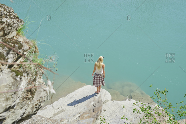 Beautiful girl exploring beautiful blue freshwater river on summer adventure vacation in nature