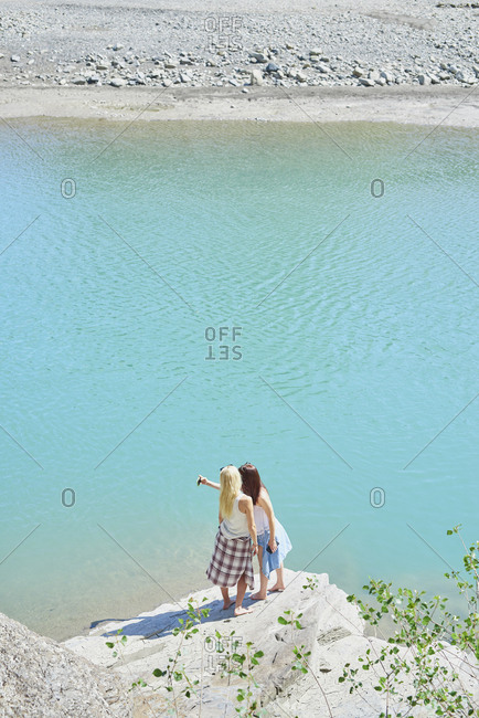Beautiful girl friends taking smart phone selfies beautiful blue freshwater river on summer adventure vacation in nature