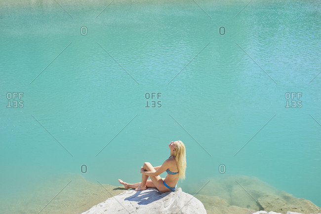 Beautiful girl tanning to wild swim in beautiful blue freshwater river on summer adventure vacation in nature