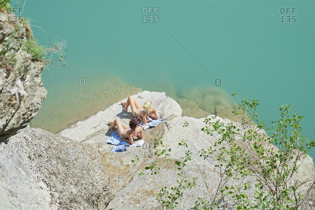Beautiful girl friends tanning to wild swim in beautiful blue freshwater river on summer adventure vacation in nature