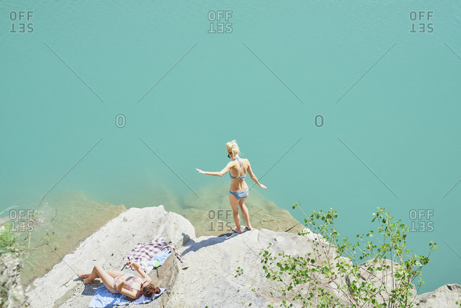 Beautiful girl friends testing water to wild swim in beautiful blue freshwater river on summer adventure vacation in nature