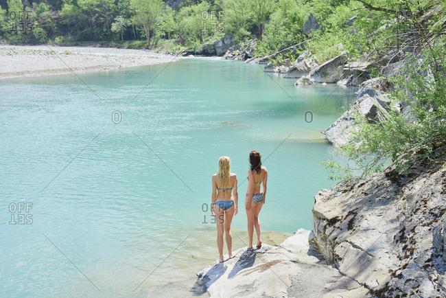 Adventure girl friends enjoying view of beautiful blue freshwater river stream wild landscape