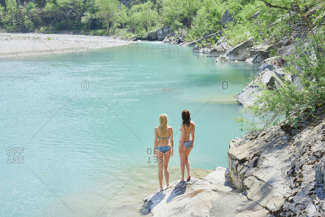 Adventure girl friends enjoying view of beautiful blue freshwater river stream wild landscape
