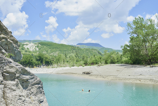 Girl friends wild swimming in beautiful blue freshwater river on travel adventure