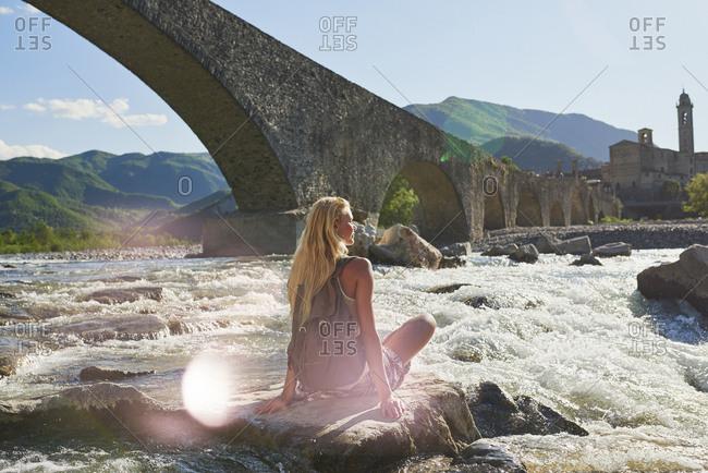 Travel adventure woman sitting on rock in river enjoying scenery view historical european town