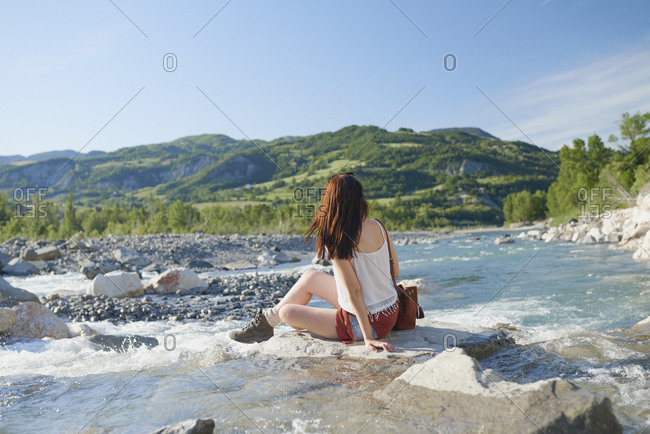 Travel adventure woman sitting on rock in river enjoying scenery view on vacation