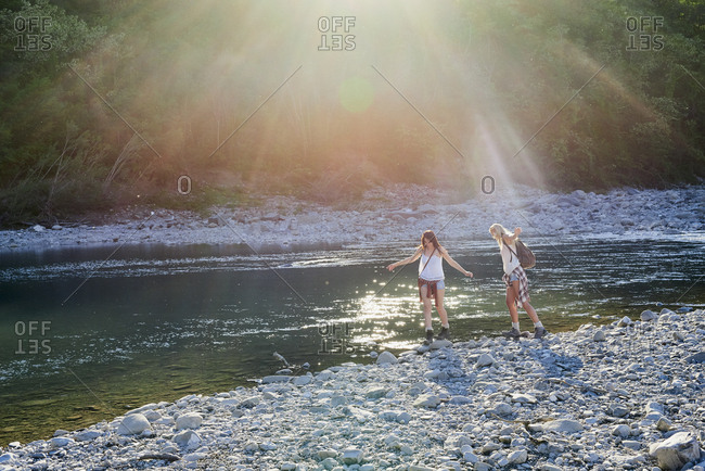 Adventure girl friends exploring river bank in countryside nature travel vacation