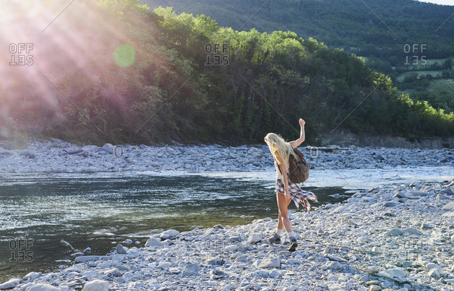 Adventure girl exploring river bank in countryside nature travel vacation sun flare