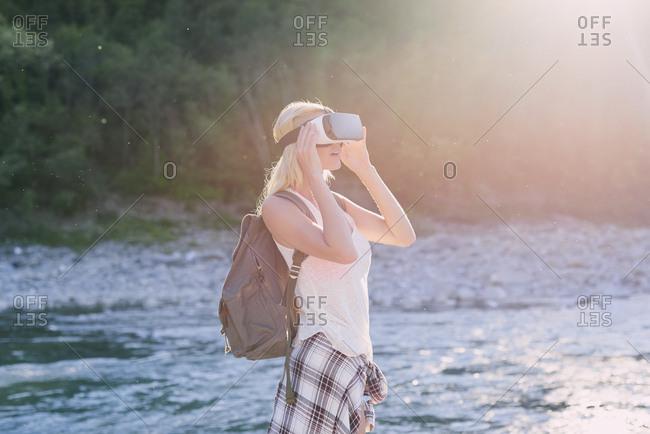 Adventurous woman wearing VR headset in beautiful outdoor landscape