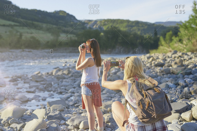 Travel girl friends taking photos smart phone vintage camera exploring river in nature on adventure vacation