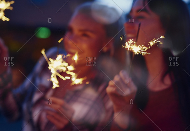 Beautiful Girl friends celebrating with sparklers having fun laughing for holiday friendship