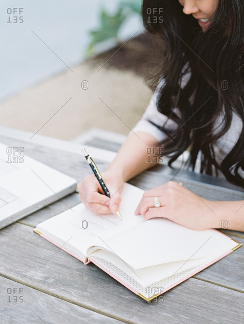 Woman writing in a journal at a picnic table