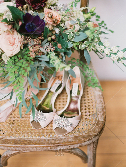 Open-toe formal shoes and a floral bouquet on an antique chair