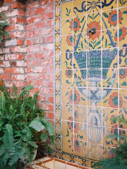 Mosaic tile fountain on a brick wall in a garden